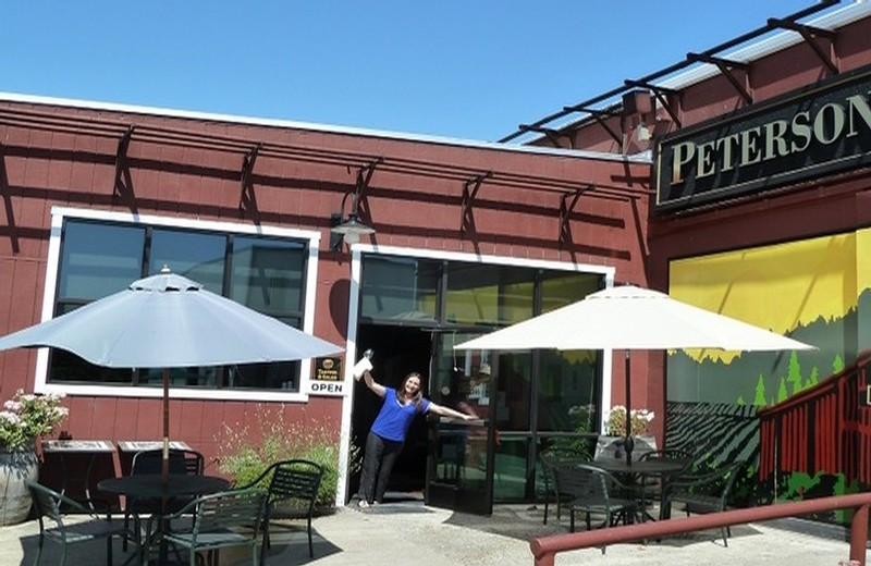 A view of our tasting room patio with umbrella-shaded seating and welcoming tasting room staff