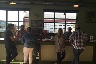 Visitors at the tasting room bar enjoy chatting and tasting wines with Jamie and Fred Peterson